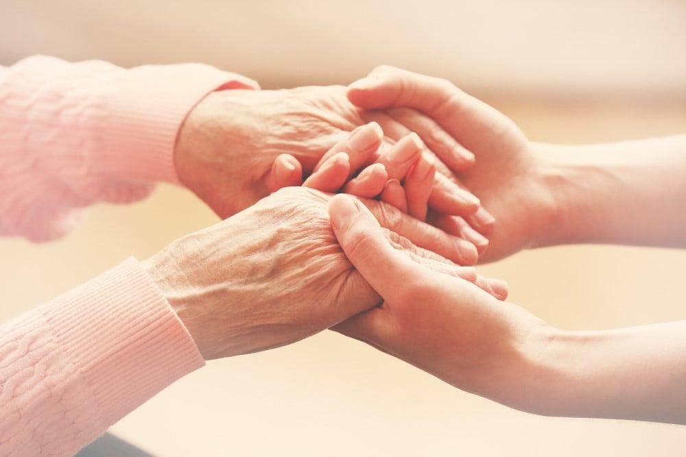 Ældre kvinde der holder en yngre kvinde i hånden