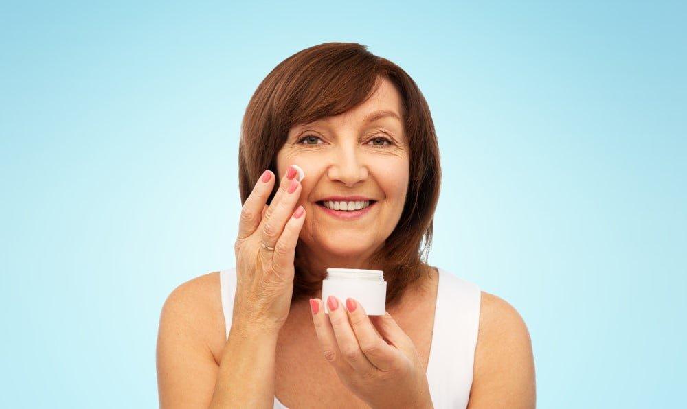 Kvinde der smører creme i ansigtet