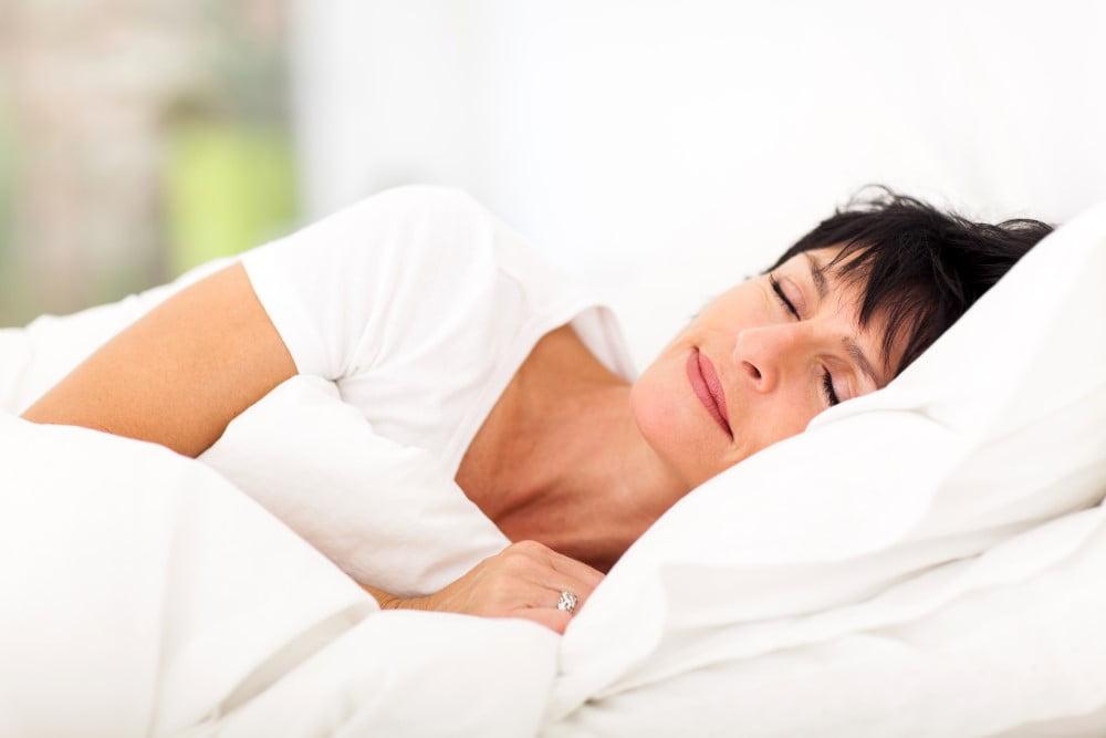 Moden kvinde i sin seng